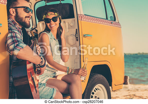 Summer tunes. Happy young couple enjoying time together while sitting in their retro minivan with sea in the background - csp28207046