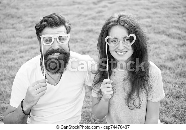 Summer vacation. Emotional couple radiating happiness. Happy together. Couple in love cheerful youth booth props. Love story. Couple relaxing green lawn. Man bearded hipster and pretty woman in love - csp74470437