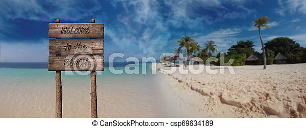 Summer Wooden Board Sign with Text, Welcome To The Beach At Beautiful Sandy Beach Tropical Island - csp69634189