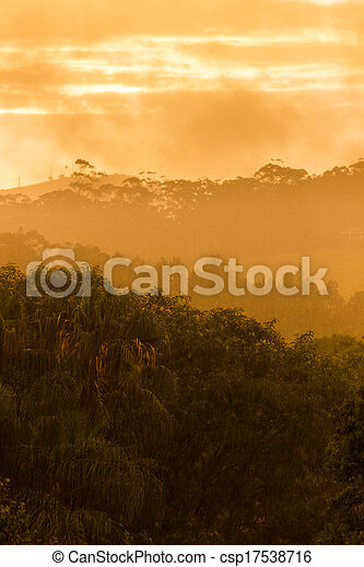 Sun breaking through clouds in rainstorm - csp17538716