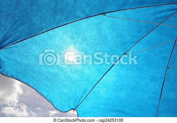Sun Filtering Through Blue Sun Umbrella - csp24253100