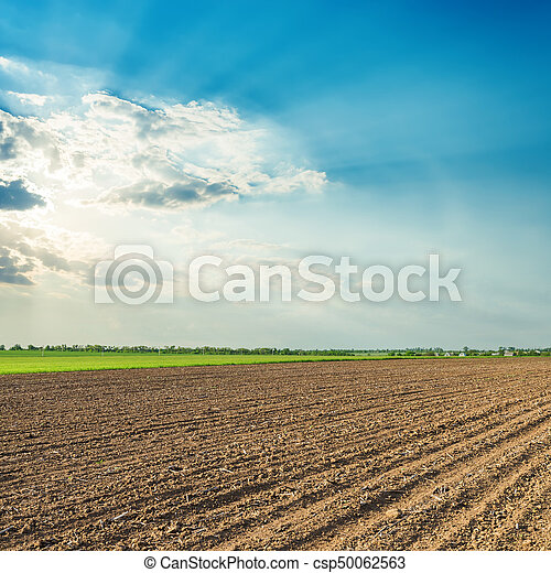 sun in clouds over black agriculture field