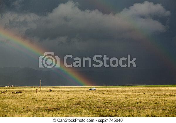 Sun shining on grassland under storym and rain - csp21745040