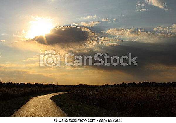 Sun through clouds on a lonely road - csp7632603