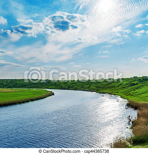 sun with clouds in blue sky over river - csp44365738