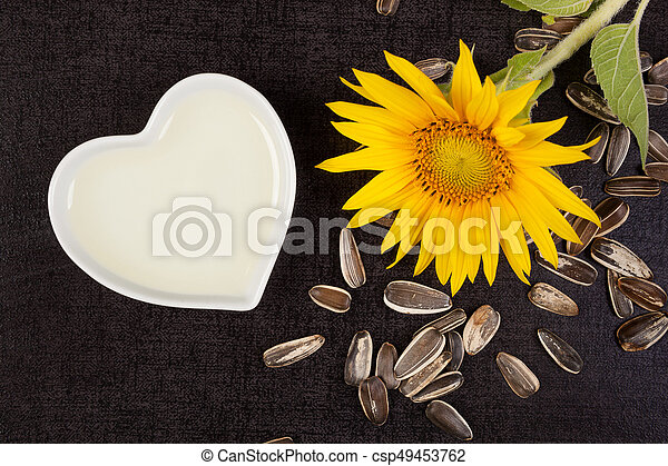Fresh sunflower plant with sunflower oil and seeds from above on black surface. Sunflower oil.