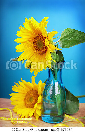 Still Life With Fresh Sunflowers In Vase On Blue Background