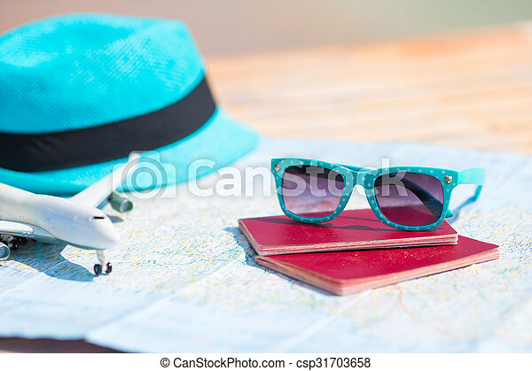 Sunglasses and passports, miniature airplane on the map. Travelling concept - csp31703658