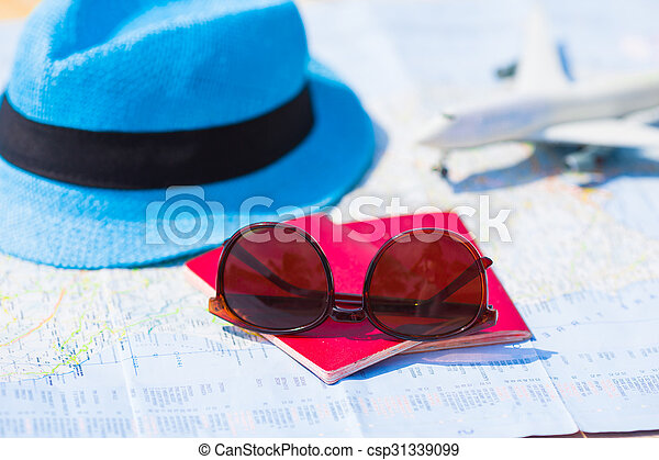 Sunglasses and passports, miniature airplane on the map. Travelling conception - csp31339099