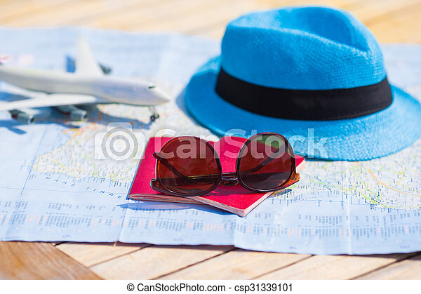 Sunglasses and passports, miniature airplane on the map. Travelling conception - csp31339101