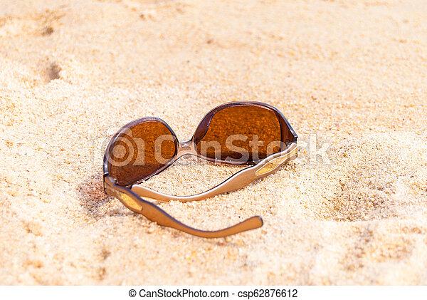 Sunglasses on the beach near the sea - csp62876612