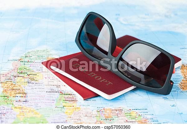 sunglasses with passports on the world map - csp57050360