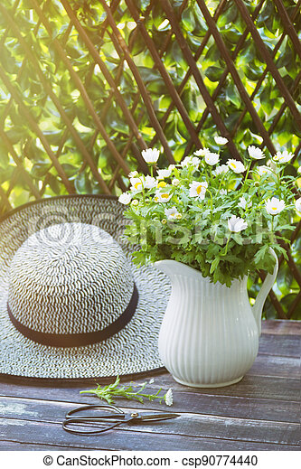 Sunhat with daisies in jug on table - csp90774440