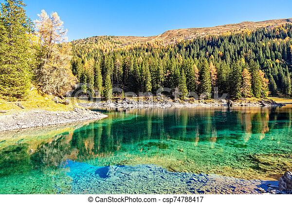 Sunny Day At Mountain Lake At Autumn Alps. Lake Obernberg is a mountain lake located in the Stubai Alps in Tyrol, Austria. - csp74788417