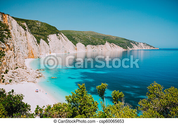 Sunny Fteri beach lagoon with rocky coastline, Kefalonia, Greece. Tourists under umbrella chill relax near clear blue emerald turquoise sea water - csp60065653
