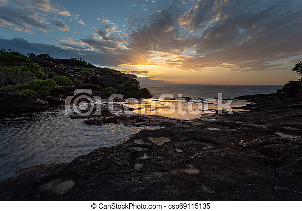 Sunrise and views over the cliffs at Curracurong creek and falls - csp69115135