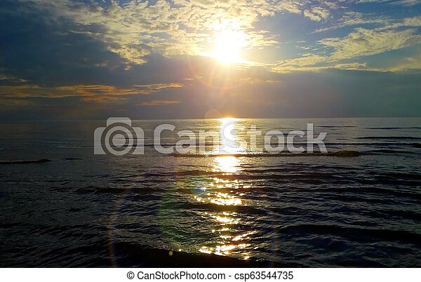 Sunrise at sea under cloudy blue sky - csp63544735