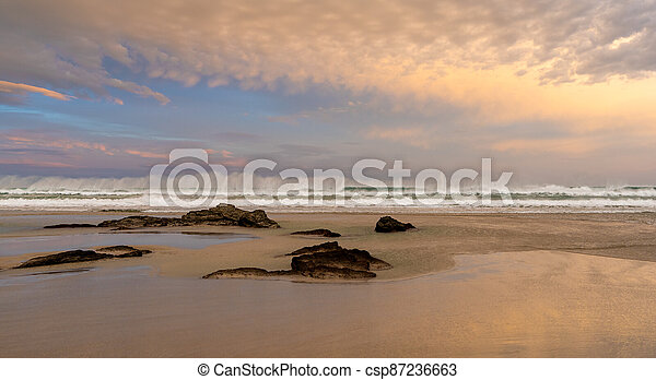 sunrise on a beautiful empty beach with waves crashing and rocks in the sand - csp87236663
