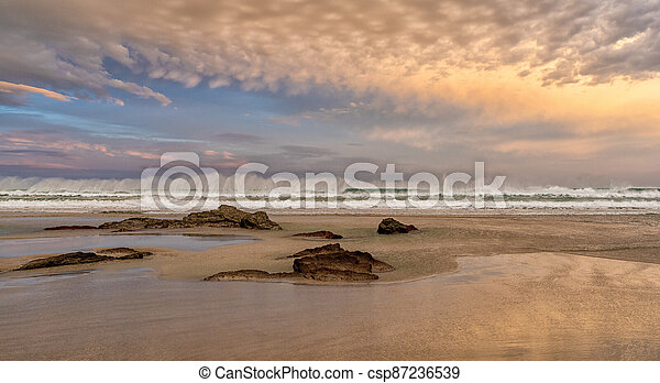 sunrise on a beautiful empty beach with waves crashing and rocks in the sand - csp87236539