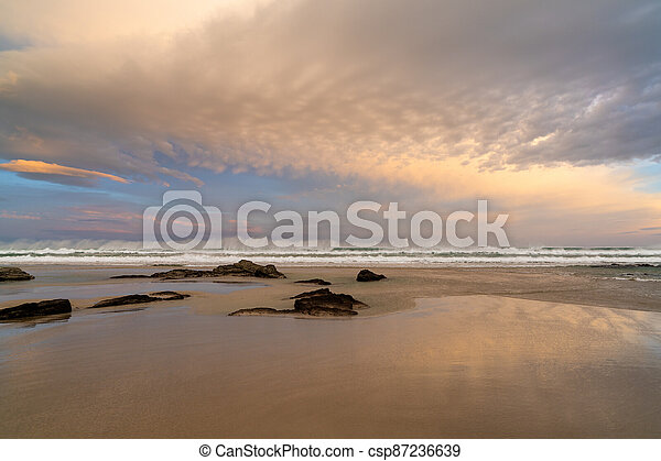 sunrise on a beautiful empty beach with waves crashing and rocks in the sand - csp87236639