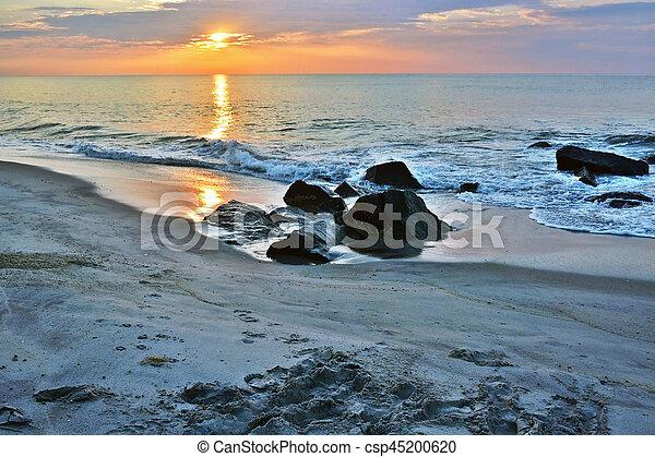Sunrise Over Rock Jetty on Beach - csp45200620