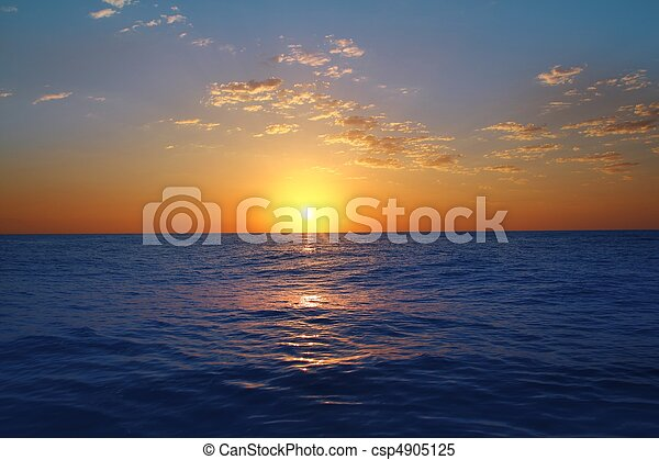 Sunrise sunset in ocean blue sea glowing sun - csp4905125