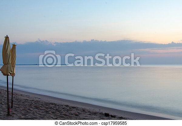 Sunrise under parasol on the beach - csp17959585