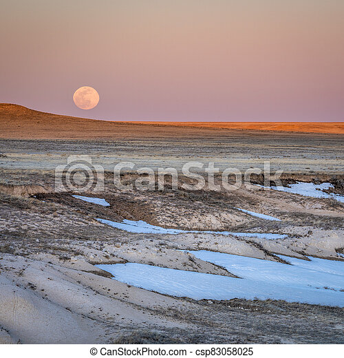 Sunset and moon rise over prairie - csp83058025