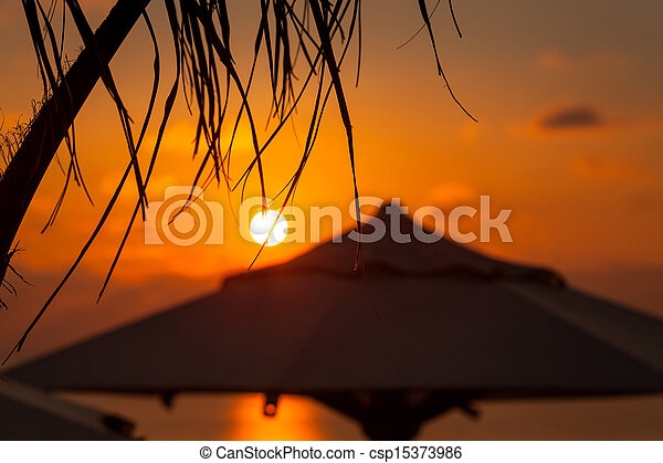 Sunset at sea. palm tree with parasol at background - csp15373986