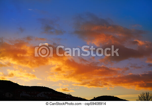 Sunset mountain silhouette with orange clouds - csp59408914