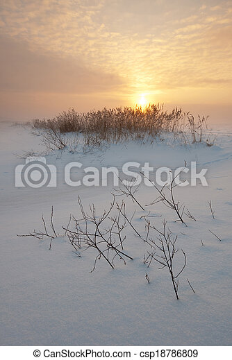 Sunset on field in winter - csp18786809