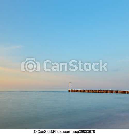 sunset on the beach with a wooden breakwater, long exposure - csp39803678