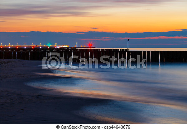 sunset on the beach with a wooden breakwater, long exposure - csp44640679
