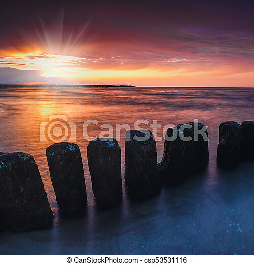 Sunset on the beach with a wooden breakwater, long exposure - csp53531116