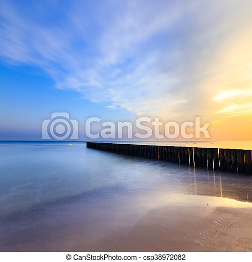 sunset on the beach with a wooden breakwater, long exposure - csp38972082