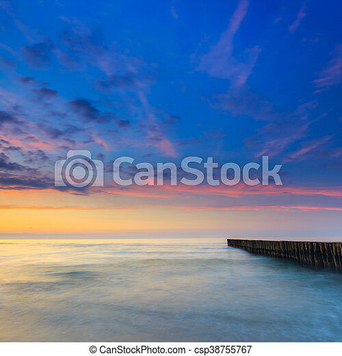 sunset on the beach with a wooden breakwater, long exposure - csp38755767