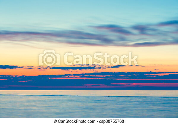 sunset on the beach with a wooden breakwater, long exposure - csp38755768