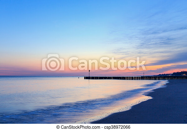 sunset on the beach with a wooden breakwater, long exposure - csp38972066