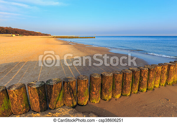 sunset on the beach with a wooden breakwater, long exposure - csp38606251