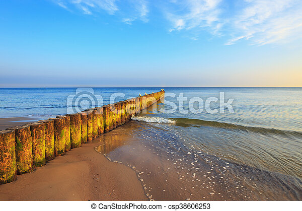 sunset on the beach with a wooden breakwater, long exposure - csp38606253