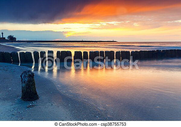 sunset on the beach with a wooden breakwater, long exposure - csp38755753