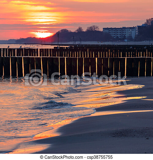 sunset on the beach with a wooden breakwater, long exposure - csp38755755