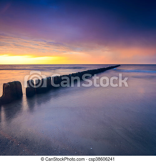 sunset on the beach with a wooden breakwater, long exposure - csp38606241