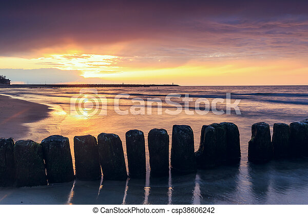 sunset on the beach with a wooden breakwater, long exposure - csp38606242