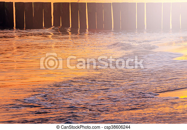 sunset on the beach with a wooden breakwater, long exposure - csp38606244