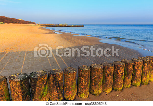 sunset on the beach with a wooden breakwater, long exposure - csp38606248