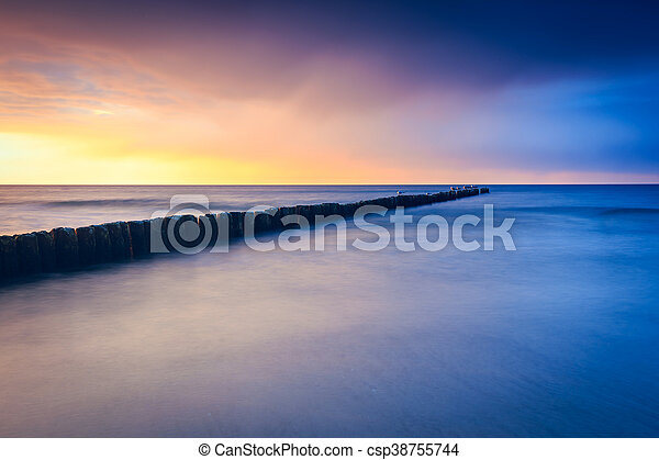 sunset on the beach with a wooden breakwater, long exposure - csp38755744