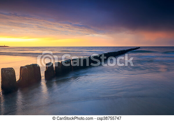 sunset on the beach with a wooden breakwater, long exposure - csp38755747