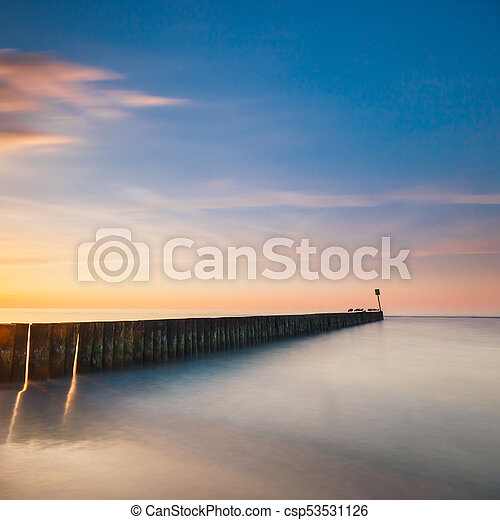 Sunset on the beach with a wooden breakwater, long exposure - csp53531126