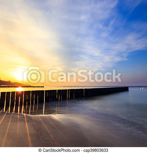 sunset on the beach with a wooden breakwater, long exposure - csp39803633